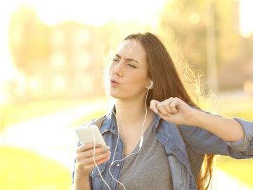 Chica disfruta escuchando música en el móvil