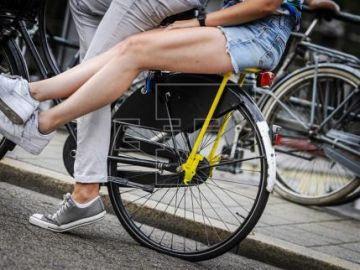 Moverse en bici y cobrar por ello, nueva idea de Holanda contra los coches Dos personas montan en bicicleta por las calles de Amsterdam