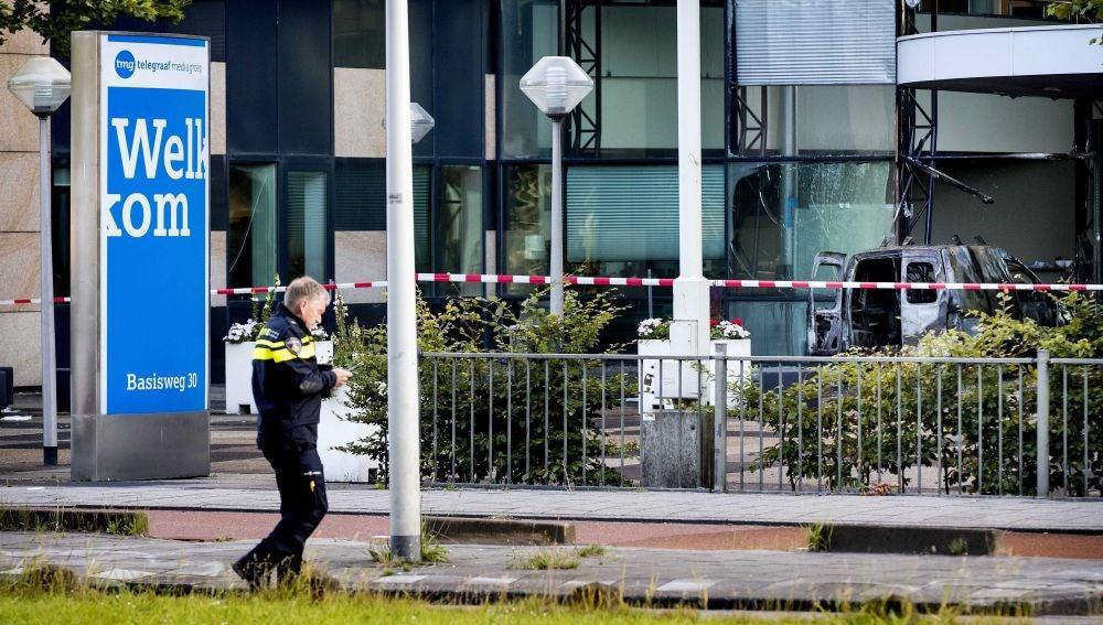 Un oficial de la policía pasa delante de la furgoneta que se empotró contra la sede del diario 'De Telegraaf' en Ámsterdam