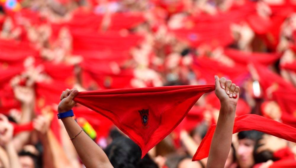 Cientos de personas festejan en la Plaza del Castillo de Pamplona, con sus pañuelos rojos alzados