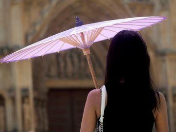 Una mujer se protege con una sombrilla de las altas temperaturas