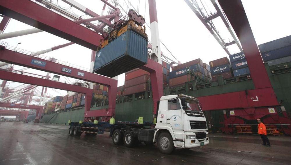 Un operario observa las labores de carga de un contenedor en un camión en el puerto de Qingdao