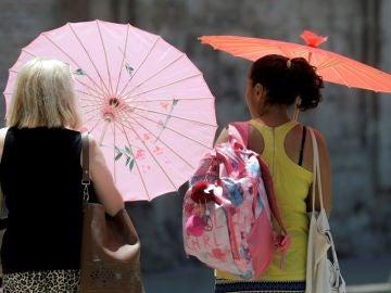 Dos mujeres se protegen del calor con unas sombrillas.