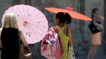 Imagen de archivo de dos mujeres protegiéndose del calor con unas sombrillas