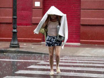 Una mujer camina bajo la lluvia durante una tormenta