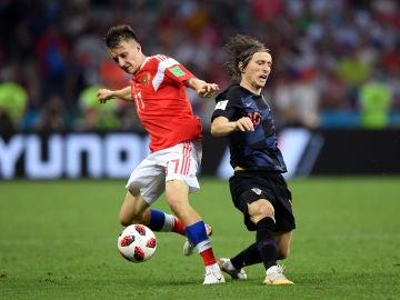 Golovin y Modric disputan la posesión del balón