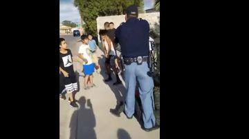 Un policía amenaza con su pistola a unos niños