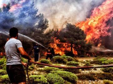 Varios bomberos y voluntarios luchan contra las llamas en un incendio en Verori, cerca de la ciudad de Loutraki (Grecia)