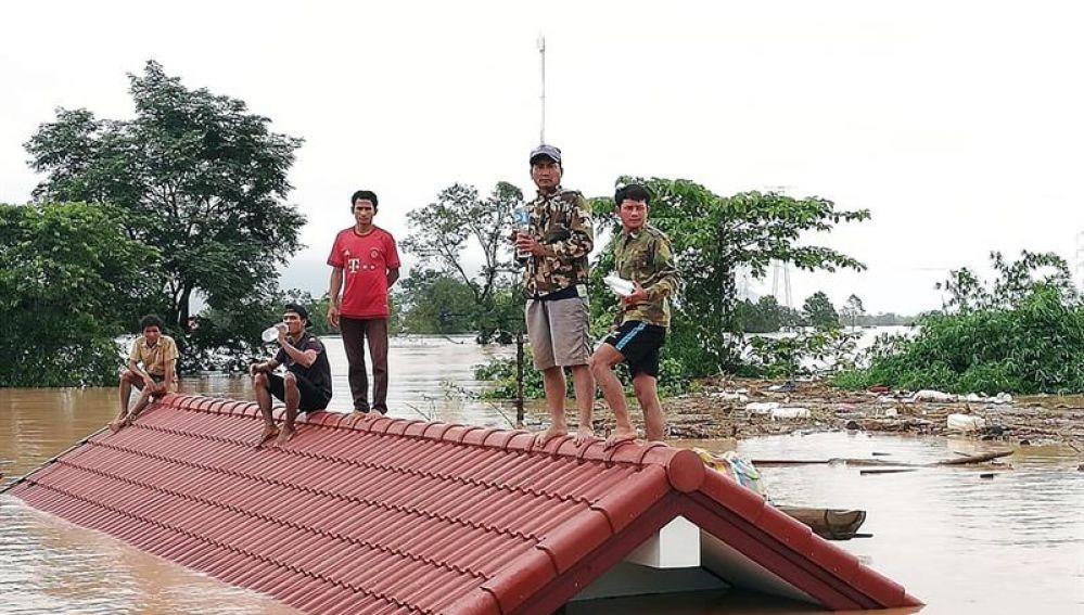 Un grupo de personas aguarda en lo alto de un tejado en una zona inundada tras el derrumbe de una presa