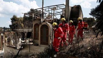 Miembros de la Cruz Roja buscan desaparecidos por las casas