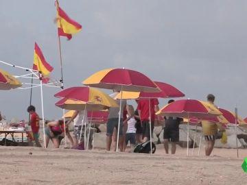 Unas 30 personas han llenado esta playa de Montgat, Barcelona, con sombrillas con la bandera de España