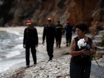 Varios bomberos buscan a desaparecidos mientras una mujer sostiene un ramo de flores tras el incendio forestal de Mati