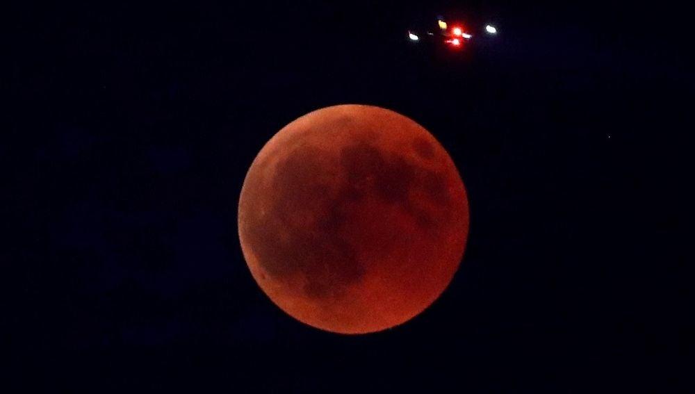 Imagen de un avión que pasa sobre la Luna durante el eclipse lunar más largo del siglo XXI