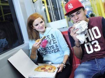 Dos pasajeros en el interior de un convoy de la línea U6, la más antigua de Viena, comen pizza y kebab