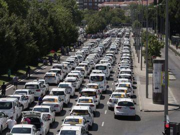 Un grupo de taxis permanecen concentrados a su paso por el ministerio de Fomento