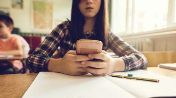 Una estudiante con un móvil durante una clase