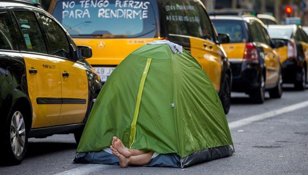Un taxista acampa junto a la hilera de taxis en el centro de Barcelona