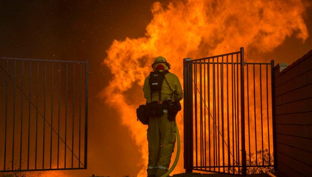 Un bombero trata de apagar un incendio en Corona, California.