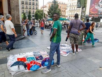 Un grupo de manteros muestra sus productos al público que transita por la Gran Vía de Madrid