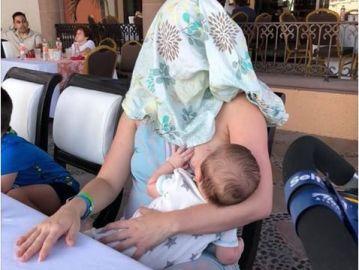 Mujer cubierta mientras amamanta a su hijo