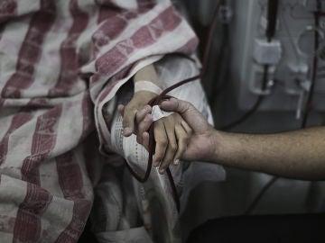 Un paciente palestino es consolado mientras recibe tratamiento en el área de diálisis del hospital al-Shifa, en Gaza