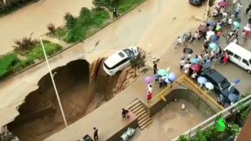 Un coche, a punto de caer a un socavón en China provocado por las fuertes lluvias