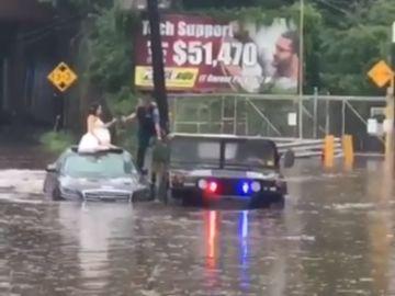 La novia escapa de la inundación con el vestido de novia puesto