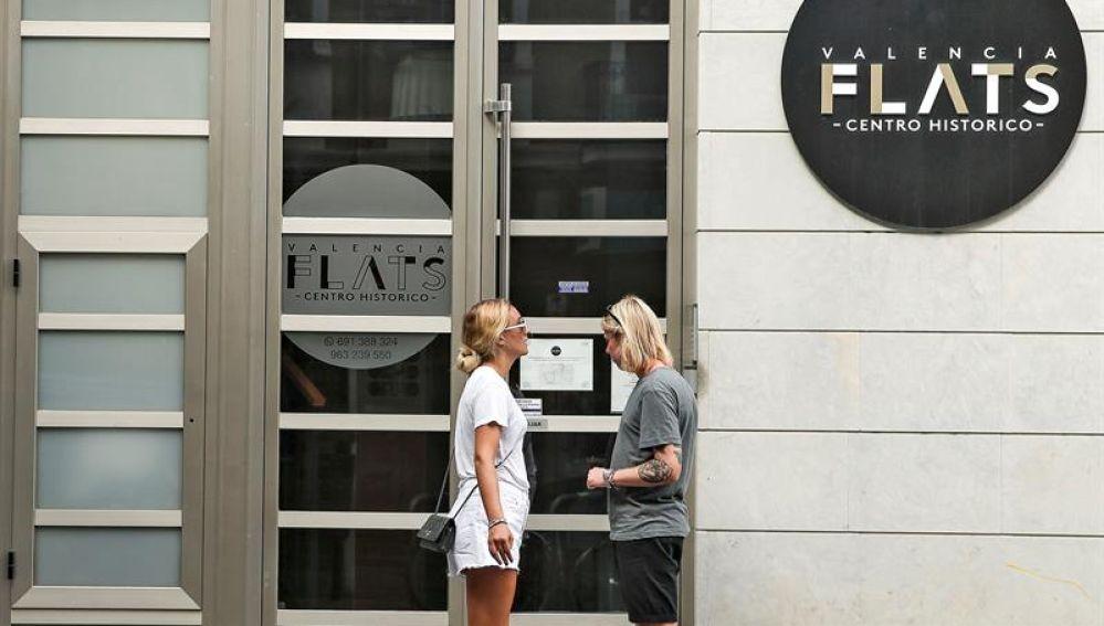 Una pareja de turistas se dispone a entrar en edificio de apartamentos
