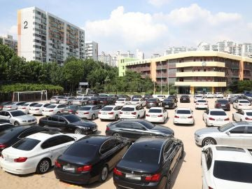 Vista de decenas de vehículos BMW permanecen aparcados en el patio de un colegio en Seúl
