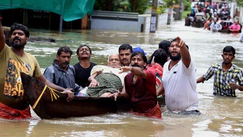 Un grupo de hombres evacua a un anciano en una barca durante las inundaciones sufridas en India