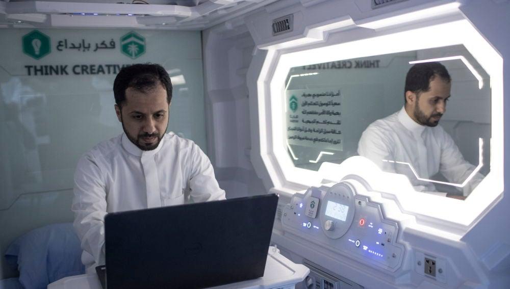 Un peregrino hajj musulmán utiliza su ordenador dentro de su habitación/cápsula en un hotel móvil dispuesto en La Meca