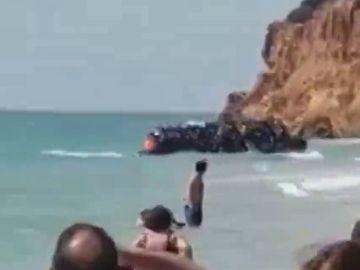 BORRADOR Unos 50 migrantes llegan a una playa de Chiclana en una zodiac ante la atenta mirada de los bañistas
