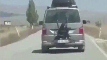 Niña atada a la parte trasera de un coche