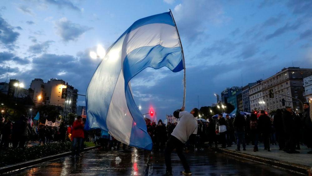 Un joven ondea una bandera argentina durante una marcha universitaria en la ciudad de Buenos Aires