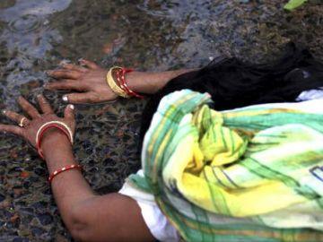 Una devota india reza recostada en el río Ganges