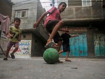Niños palestinos jugando fútbol en un campo de refugiados