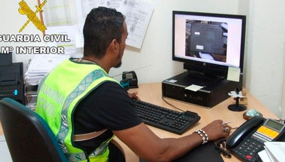 Un agente de la Guardia Civil incautando material pornográfico infantil