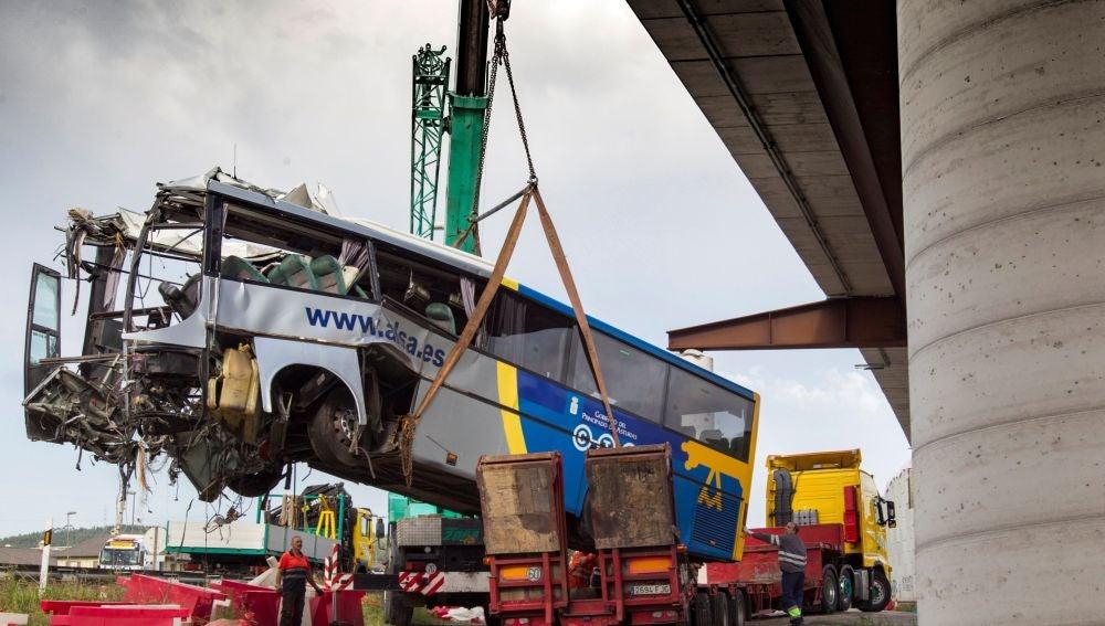 Una grúa retira los restos del autobús de la compañía Alsa que ayer se empotró contra una pilastra de hormigón
