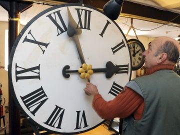 Peter Leonardy examina un reloj fabricado alrededor del año 1900 por la compañía Benedikt Schneider