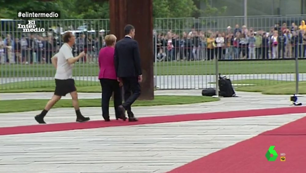 Pedro Sánchez y Angela Merkel caminan con Mariano Rajoy detrás