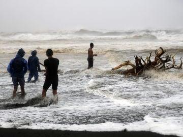 Varios filipinos juegan con las olas en la ciudad de Aparri, Filipinas, ocasionadas por el paso de Mangkhut