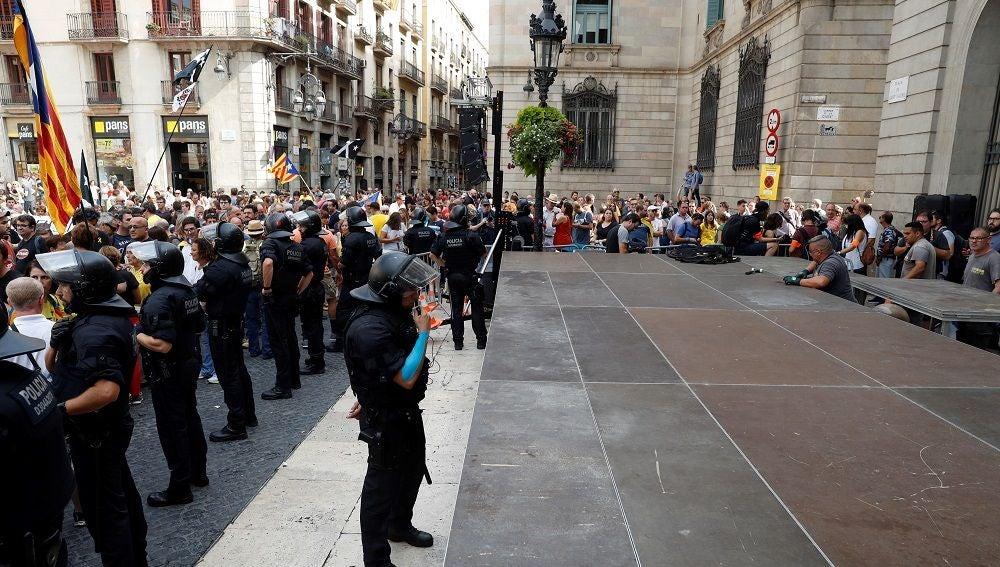 Efectivos de los Mossos d'Esquadra se interponen ante un grupo de soberanistas que se concentraron en la plaza de Sant Jaume