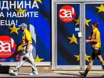 Transeúntes caminan frente a la oficina de la coalición que apoya el próximo referéndum en Skopje