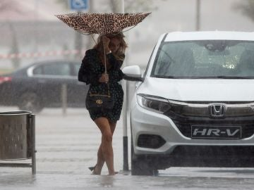 Una mujer sujeta el paraguas intentando que no se le vuele debido al viento
