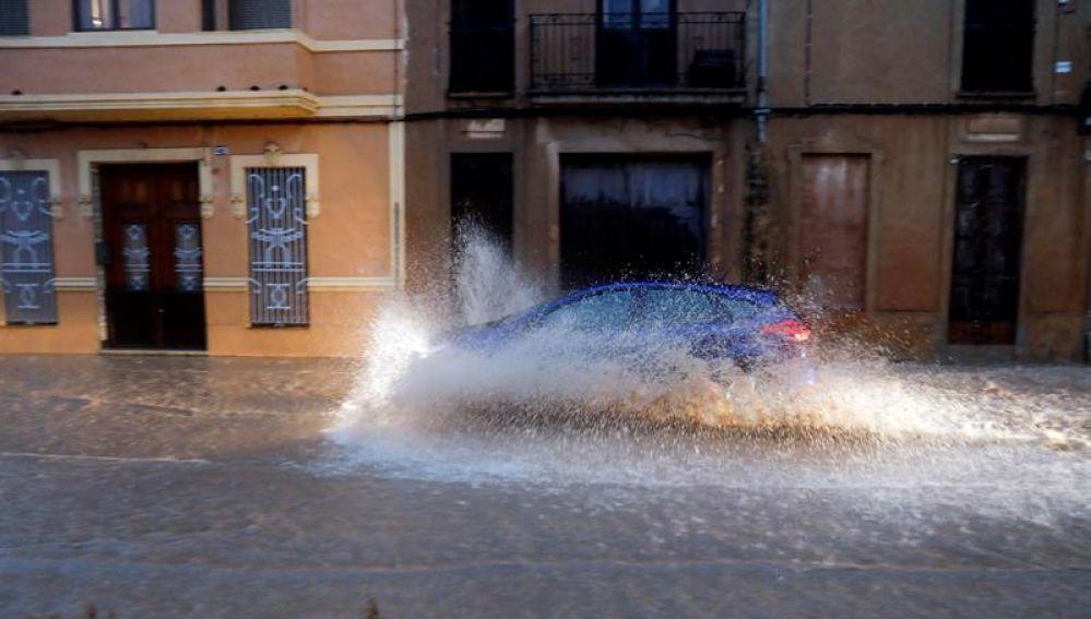 Un vehículo circula por una calle anegada de Valencia