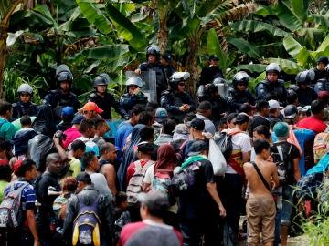 Policías antimotines dejan pasar a cientos de migrantes