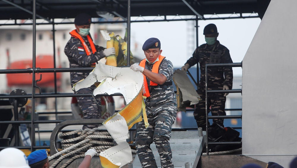 Equipo de emergencias cargando un trozo del avión siniestrado de Lion Air