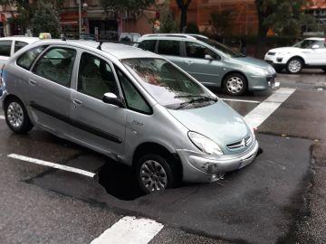 Un coche queda encajado en un socavón en Madrid