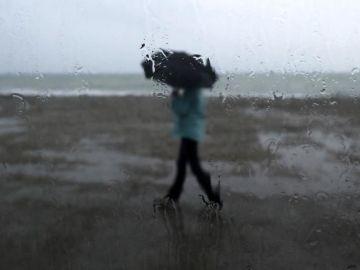 Un hombre se protege de la lluvia