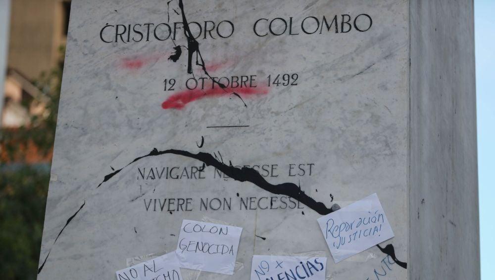 Imagen de la pintura arrojada y de los carteles pegados a la estatua de Cristóbal Colón